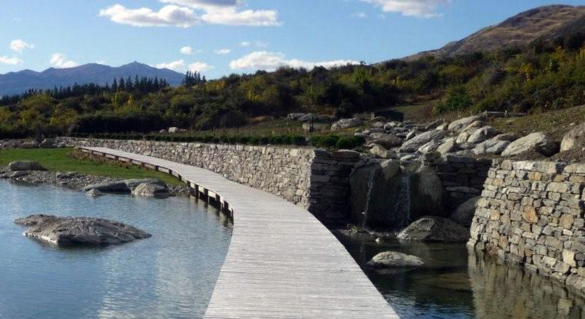 a boardwalk passes between a created waterfall and large artificial tarn, leading the eye to distant mountains